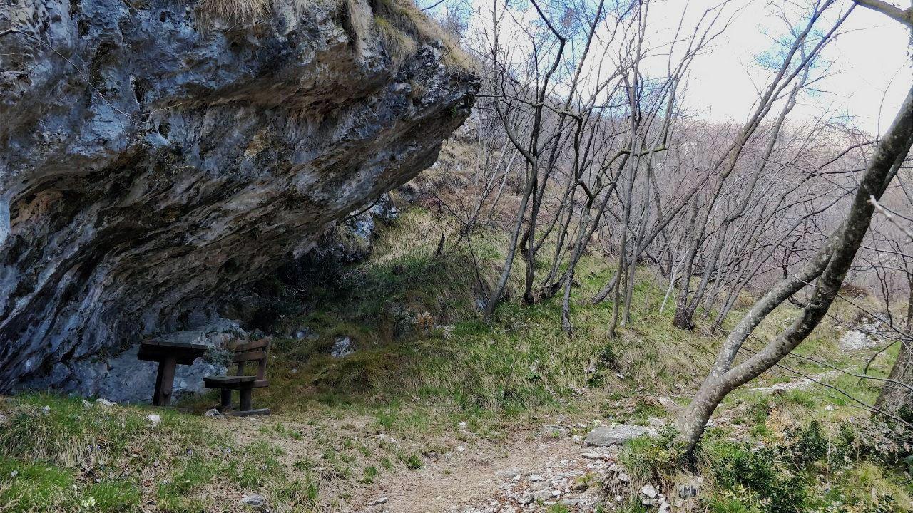 Sentiero di montagna, grossa roccia e panchina di legno